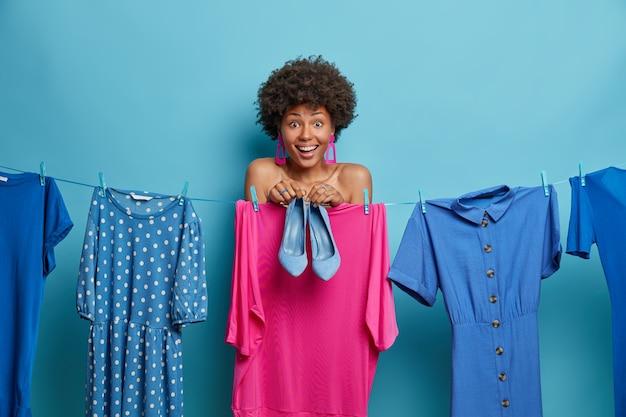 Poziome ujęcie szczęśliwej kobiety afroamerykańskiej sukienki do pracy lub wakacji, pozuje w pobliżu mokrej pranej odzieży na linie, wybiera strój pasujący do butów, ma pozytywny nastrój, na białym tle na niebieskiej ścianie.