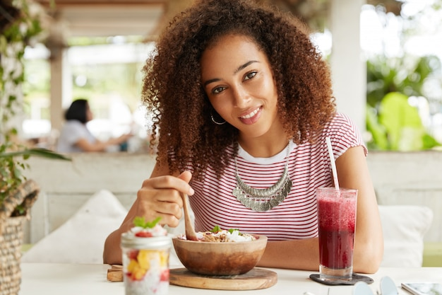 Poziome ujęcie szczęśliwej kobiety rasy mieszanej z fryzurą afro ubraną w swobodną koszulkę, je sałatkę owocową i pije smoothie w lokalnej restauracji, zadowolona z dobrej obsługi, lubi wolny czas
