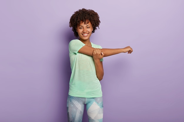 Poziome ujęcie szczęśliwej sportowej kobiety afro american rozciąga ręce przed treningiem, uśmiecha się radośnie, ubrana w aktywny strój, ma elastyczne ciało