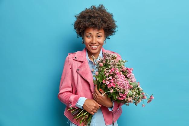 Poziome ujęcie szczęśliwej, uśmiechniętej młodej kobiety afro american trzyma duży bukiet ładnych kwiatów radość, że wiosna wreszcie nadeszła, nosi stylową różową kurtkę odizolowaną na niebieskiej ścianie