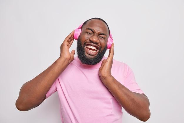 Poziome ujęcie szczęśliwy przystojny mężczyzna trzyma ręce na słuchawkach stereo lubi ulubioną muzykę przechyla głowę ubrany w casual t shirt na białym tle nad szarą ścianą