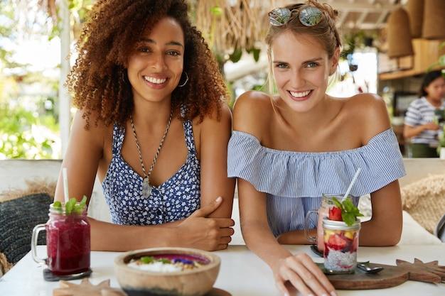 Poziome ujęcie szczęśliwych kobiet ma wesołe miny, siedzą blisko siebie w przytulnej kawiarni, otoczone koktajlami i deserem, przypadkowo spotykają się w kurorcie. ludzie i relacje