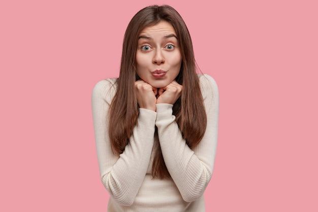 Poziome ujęcie uroczej kobiety wydyma usta, trzyma ręce pod brodą, ma atrakcyjny wygląd, pozytywny wyraz