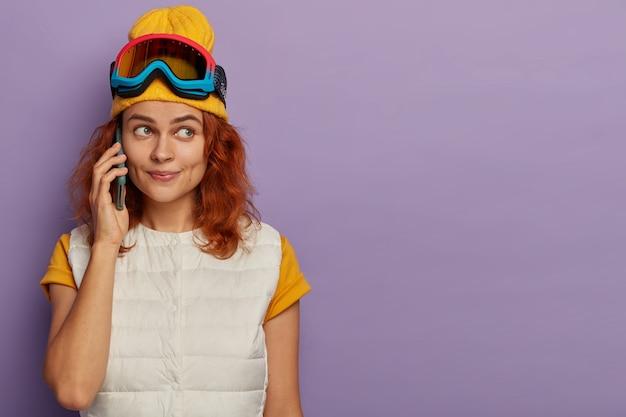 Poziome ujęcie uroczej młodej rudej kobiety w ośrodku narciarskim, dzwoni, nosi żółty kapelusz i białą kamizelkę, stoi w pomieszczeniu nad fioletową ścianą