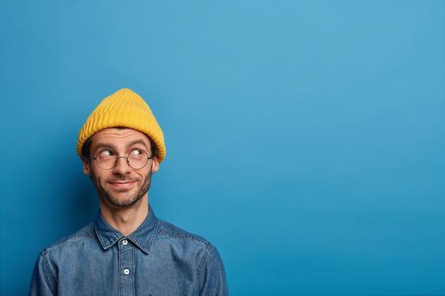Poziome ujęcie wesołego zadowolonego mężczyzny wygląda z rozmarzonym, zadowolonym wyrazem twarzy, ma zamiar coś zrobić, ubrany w stylowe ubranie