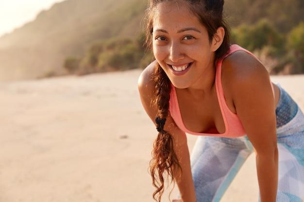 Poziome ujęcie wesołej fitness kobiety ma piegowatą skórę, ciemny warkocz, ubrana w strój sportowy i przyjemny uśmiech