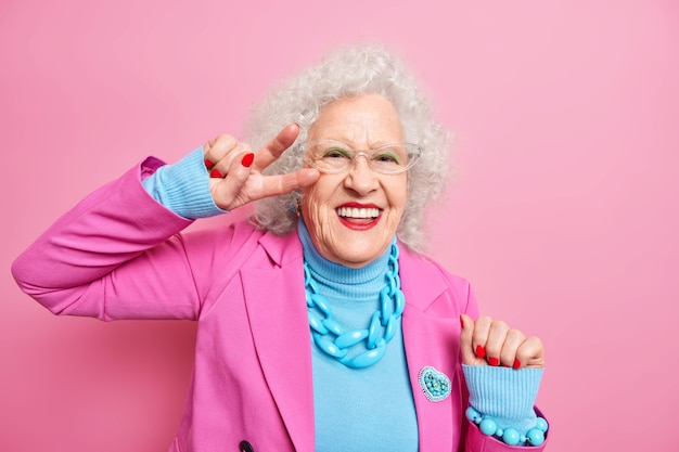 Poziome ujęcie wesołej pomarszczonej kobiety sprawia, że gest pokoju uśmiecha się z radością, ma jasny makijaż i manicure ubrany w modne ubrania