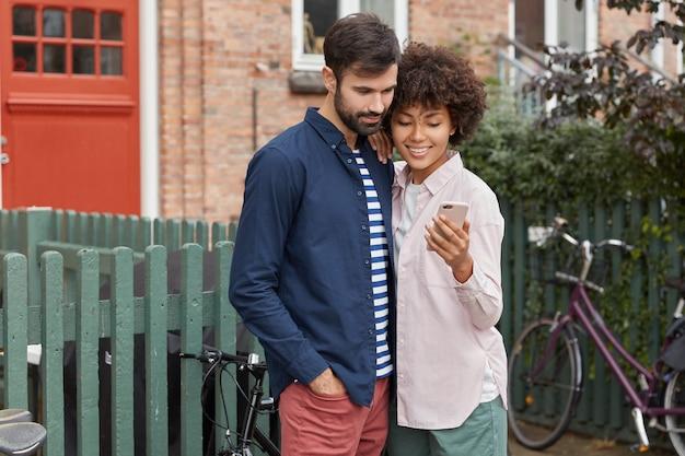 Poziome ujęcie wesołej rasy mieszanej młoda kobieta i mężczyzna czytać informacje na telefonie komórkowym
