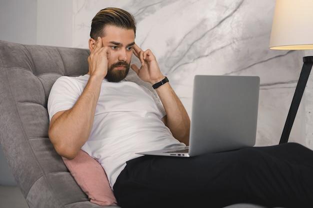 Poziome ujęcie wewnętrzne sfrustrowanego, przygnębionego, młodego nieogolonego biznesmena używającego przenośnego komputera do pracy zdalnej, zestresowanego z powodu problemów, masowania skroni, silnego bólu głowy