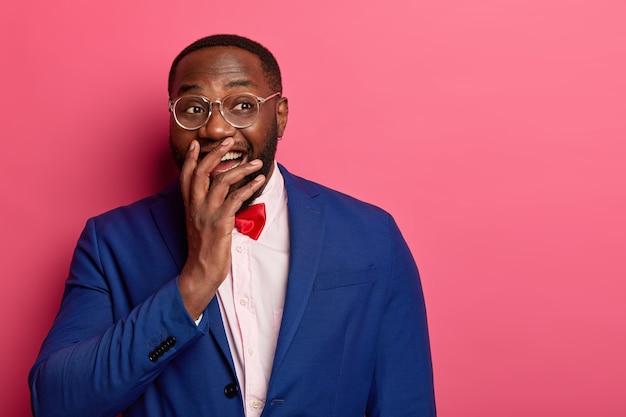 Poziome ujęcie zabawnego biznesmena w stroju wizytowym chichocze radośnie, zakrywa usta, nie mogę przestać się śmiać, słyszy zabawną historię, nie spuszcza wzroku