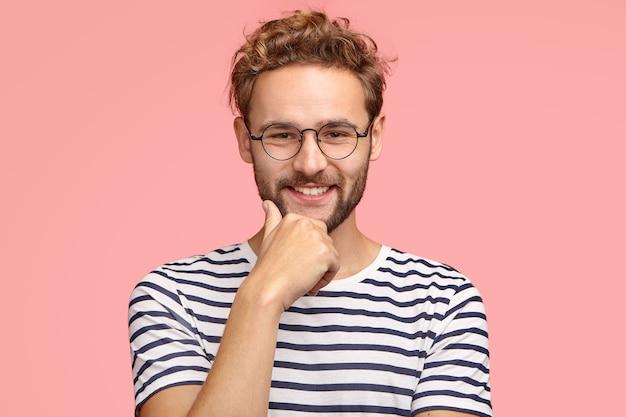 Poziome ujęcie zadowolonego, pewnego siebie faceta z przyjemnym uśmiechem, trzymającego rękę na brodzie