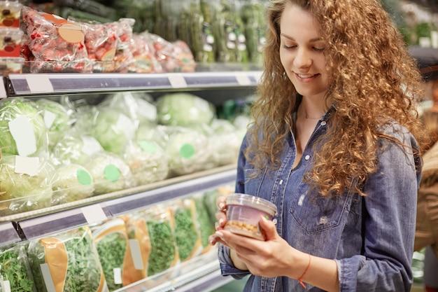 Poziome ujęcie zadowolonej kobiety kupuje jedzenie w supermarkecie, czyta informacje o produkcie, wybiera niezbędny produkt do przygotowania kolacji, będąc w dziale warzywnym. koncepcja ludzie i zakupy