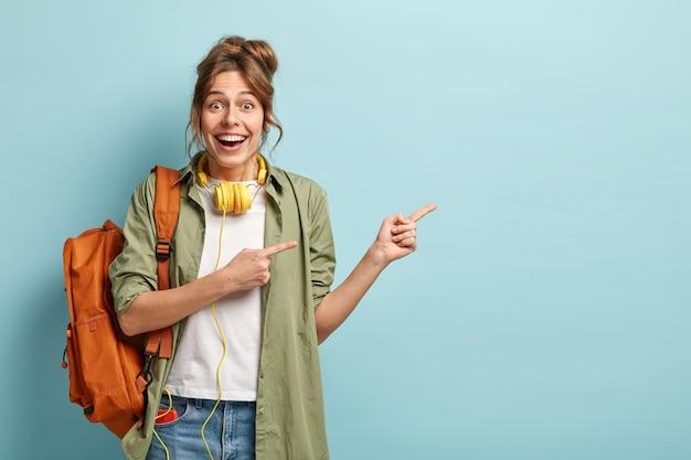 Poziome ujęcie zadowolonej kobiety rasy kaukaskiej wskazuje na bok z obu przednich palców, reklamuje coś na bok
