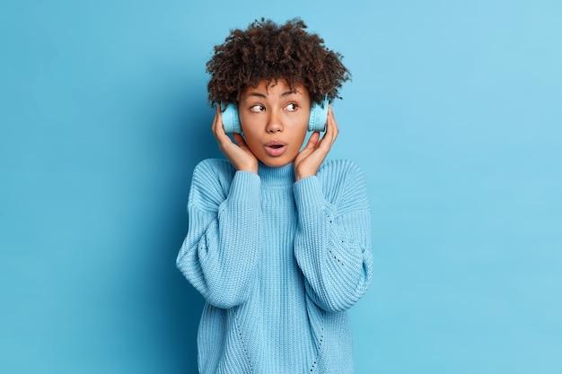 Poziome ujęcie zaskoczonej młodej afroamerykanki trzyma ręce na słuchawkach stereo, słucha ulubionej muzyki, ubranej w swobodny sweter z dzianiny