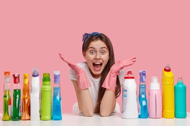 Poziome ujęcie zdumionej, uradowanej kobiety rozkładającej ręce, zakładającej rękawiczki ochronne, siadającej przy stole z wieloma detergentami