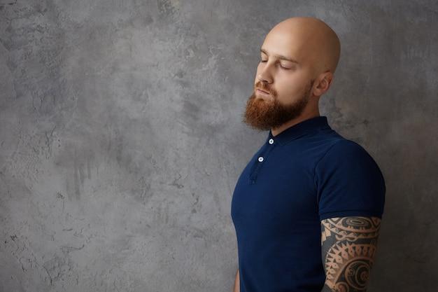 Poziome ujęcie zmęczonego męskiego fryzjera z tatuażem na ramieniu i rozmytą rudą brodą zamykającą oczy, sennym i wyczerpanym po ciężkim dniu pracy, pozującego odizolowanego od pustej ściany