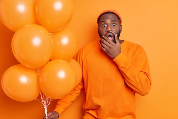 Poziome ujęcie zszokowanego brodatego mężczyzny trzymającego brodę, wpatrującego się w oczy, nie spodziewa się gratulacji od byłej dziewczyny trzymającej kilka nadmuchanych balonów ubranych w pomarańczowy strój