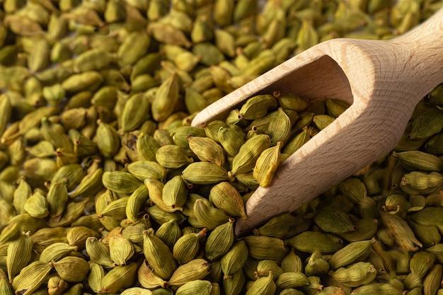 Poziome zbliżenie na nasiona kardamonu z drewnianą gałką