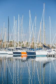 Poziome zdjęcie luksusowych i efektownych jachtów i żaglówek zacumowanych lub zaparkowanych w porcie marina w barcelonie, hiszpania