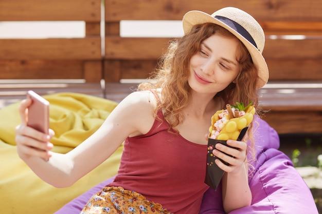 Poziome zdjęcie plenerowe młodej kobiety foxy robi selfie, siedząc na łagodnym bezramowym krześle w parku miejskim, nosi kapelusz, trzyma lody w dłoni, pozuje i patrzy na ekrany swojego smartfona