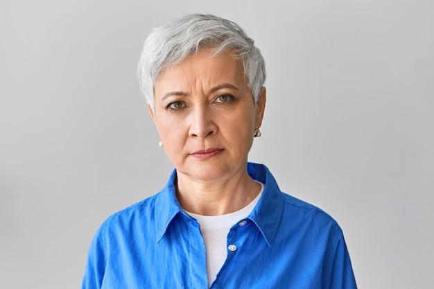 Poziome zdjęcie poważnej, zrzędliwej, siwowłosej dojrzałej bizneswoman w stylowej niebieskiej koszuli, wyrażającej negatywne emocje, marszczone brwi, niezadowolonej z późnego pracownika lub niedotrzymanego terminu