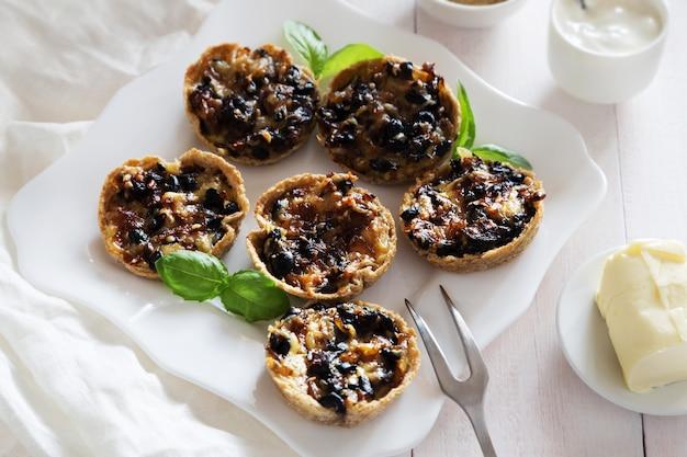Poziome zdjęcie przekąsek z pieczarkami, serem, bazylią na białym talerzu