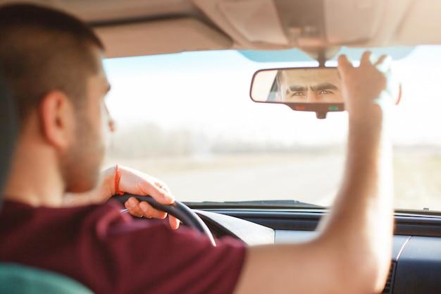 Poziome zdjęcie przystojnego nieogolonego mężczyzny o ciemnych włosach, reguluje lusterko wsteczne. atrakcyjny mężczyzna jedzie czarnym samochodem