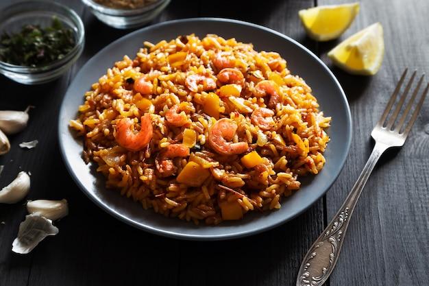 Poziome zdjęcie smażonego ryżu z krewetkami, cytryną i warzywami na szarej płytce i pościeli