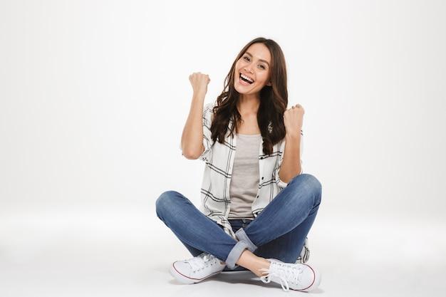 Poziome zdjęcie szczęśliwej młodej kobiety z brązowymi włosami siedzącej ze skrzyżowanymi nogami na podłodze i zaciskającej pięści jak zwycięzca, odizolowane na białej ścianie