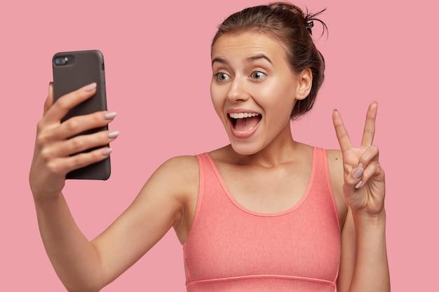 Poziome zdjęcie wesołej europejki wykonuje gest pokoju telefonu komórkowego, ubrana w różową kamizelkę, będąc w dobrym nastroju