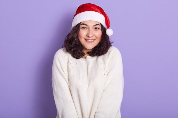 Poziome zdjęcie wnętrza wesołej nieśmiałej młodej dziewczyny z ciemnymi kręconymi włosami, noszącej akcesoria i biały sweter, cieszącą się noworocznymi wakacjami