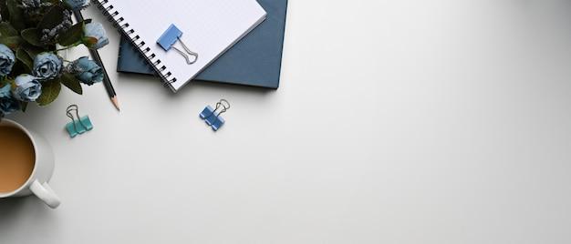 Poziomy obraz nowoczesnego biurka z filiżanką kawy, notatnikiem, doniczką z kwiatami i miejscem na kopię na białym tle.