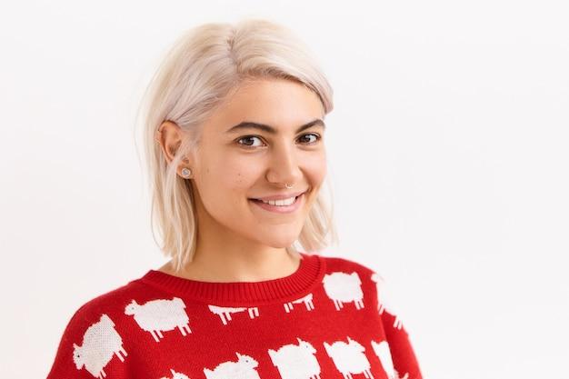 Poziomy obraz pięknej studentki z europy, radującej się z dobrych, pozytywnych wiadomości, otrzymuje znak, pozuje odizolowany w czerwonym swetrze, z uroczym uroczym uśmiechem, pokazując proste zęby