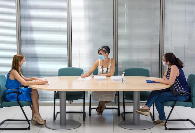 Poziomy obraz trzech kobiet w sali konferencyjnej z maskami, które utrzymują dystans społeczny z powodu covid-19 podczas spotkania roboczego