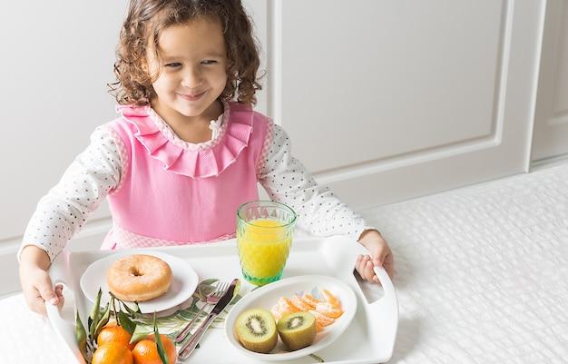 Poziomy obraz uśmiechniętej dziewczyny w różowo-białej sukni niosącej tacę ze śniadaniem w łóżku z miękkim światłem bocznym