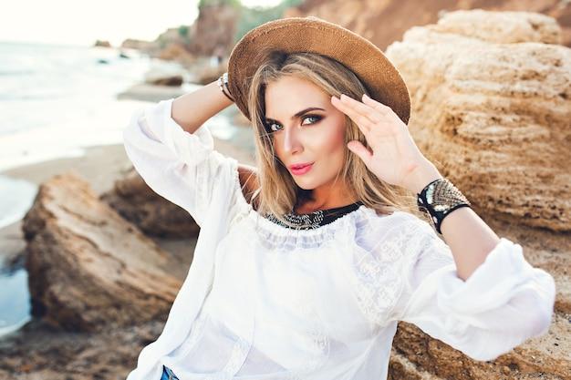 Poziomy portret atrakcyjna blondynka z długimi włosami, pozowanie do kamery na bezludnej plaży. ona patrzy w kamerę.