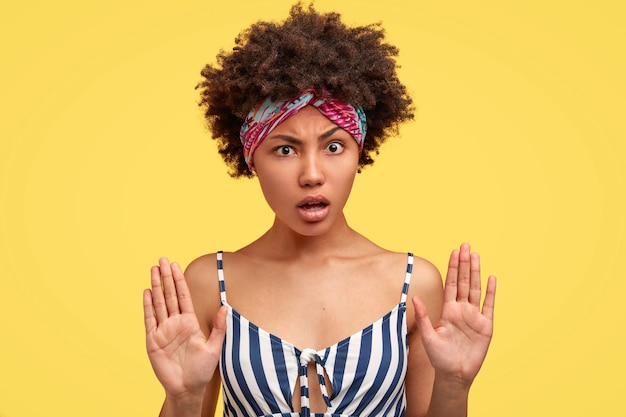 Poziomy portret atrakcyjnej młodej kobiety z fryzurą afro, ciemną, zdrową skórą, z oburzonym niezadowolonym wyrazem twarzy, pokazuje gest odmowy, odizolowany na żółtej ścianie. przestań!