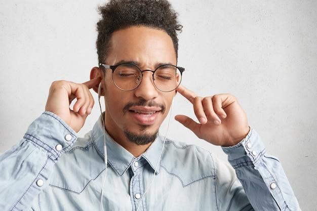 Poziomy portret ciemnoskórego, stylowego mężczyzny z fryzurą afro, zamyka oczy z radości,