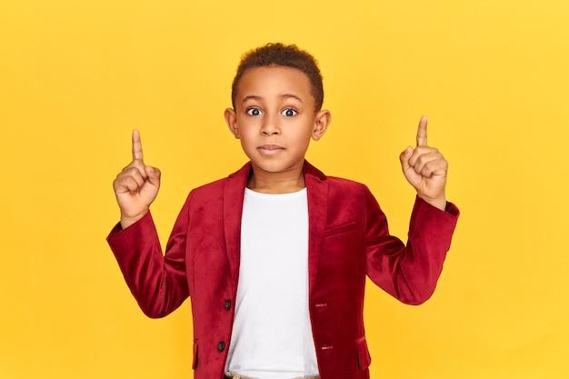 Poziomy portret emocjonalnego podekscytowanego ośmioletniego chłopca afrykańskiego wskazujący na interesujące treści