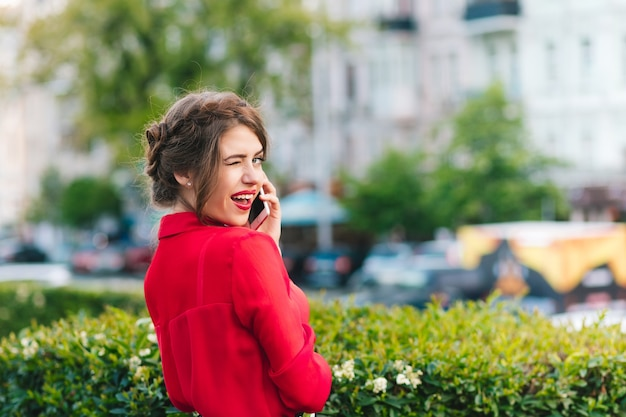 Poziomy portret ładnej dziewczyny stojącej w parku. nosi czerwoną bluzkę i ładną fryzurę. mówi przez telefon i daje znak oczami do kamery.