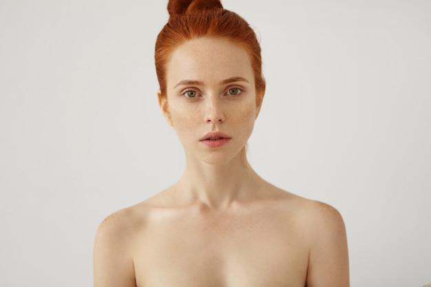 Poziomy portret nagiej, pięknej kobiety z piegowatą zdrową skórą i rudymi włosami związanymi w supeł, patrząca zielonymi oczami