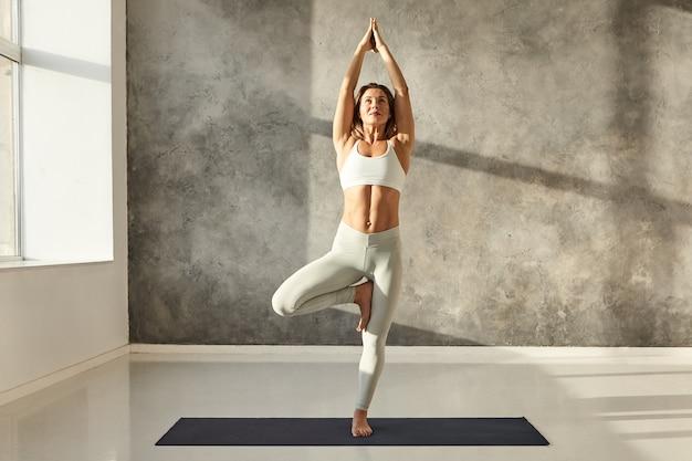 Poziomy portret pełnej długości atrakcyjnej młodej kobiety z pięknym atletycznym ciałem praktykującej jogę w stylowym biustonoszu sportowym i legginsach, wykonującej pozę jogi vrikshasana lub tree w dużej siłowni