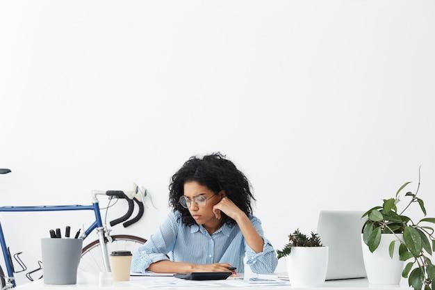 Poziomy portret poważnej ciemnoskórej bizneswoman na białym tle nad wnętrzem biura