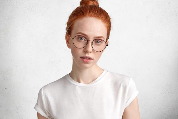 Poziomy portret poważnej rudowłosej kobiety w dużych okrągłych okularach wygląda z tajemniczym wyrazem twarzy bezpośrednio do aparatu