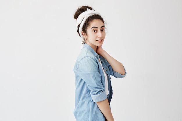 Poziomy portret pozytywnej modelki trzyma rękę na szyi, z ciemnymi i falującymi włosami w kokie, wygląda sennie, raduje się z wakacji, pozuje na białej ścianie z miejsca na kopię