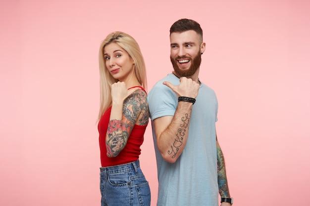 Poziomy portret pozytywnej uroczej pary stojącej tyłem do siebie i trzymając ręce podniesione, wskazując na siebie kciukami, odizolowane na różowo