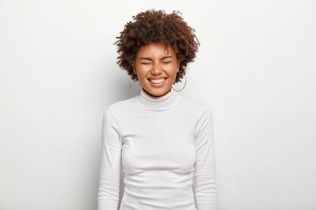 Poziomy portret radosnej afro głośno się śmieje, ma zamknięte oczy, jest w dobrym nastroju, nosi golf, odizolowany na białej ścianie. ludzie, satysfakcja, przyjemność, pochodzenie etniczne, emocje