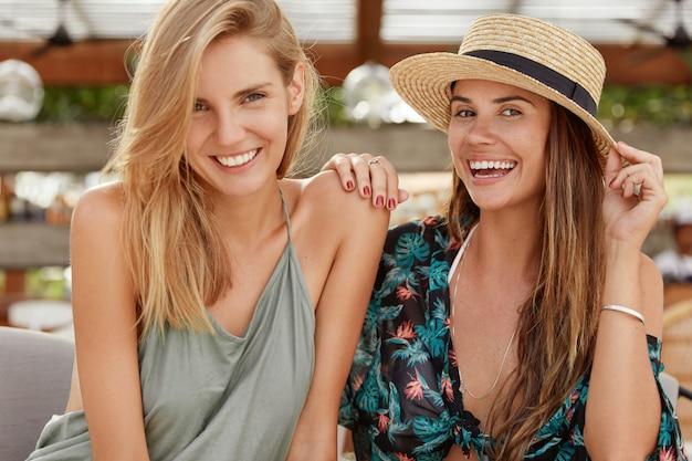 Poziomy portret szczęśliwych kobiet obejmujących się, utrzymujących związki homoseksualne, uśmiechających się szeroko, siadających na tle kawiarni. dwie lesbijki wyglądają wesoło, czują się zrelaksowane, dobrze się bawią