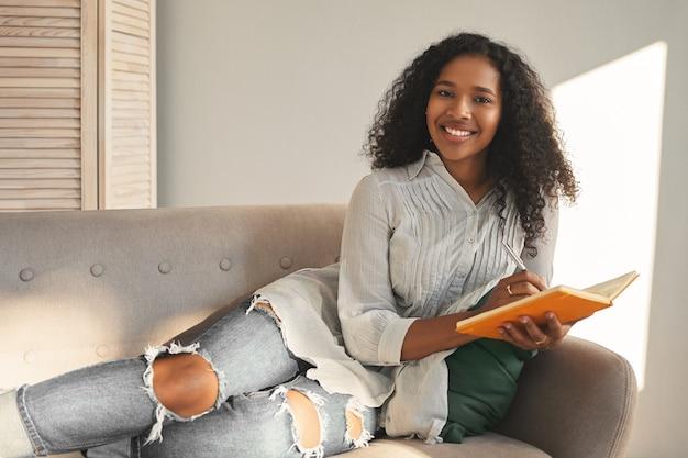 Poziomy portret uroczej pozytywnej młodej kobiety rasy mieszanej w stylowej koszuli i podartych niebieskich dżinsach, uśmiechnięta szeroko, leżąca na kanapie z pamiętnikiem, planująca wakacje, szczęśliwa i zainspirowana