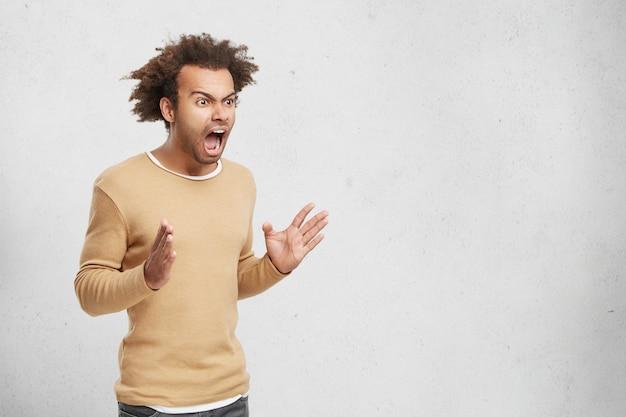 Poziomy portret wściekłego ciemnoskórego mężczyzny ma ostre włosy, nosi zwykłe ubrania,